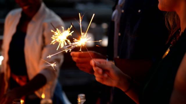 midsection of friends enjoying with sparklers - terrazza video stock e b–roll