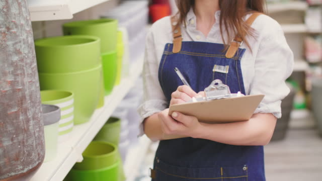 Midsection of saleswoman writing on clipboard in flower shop