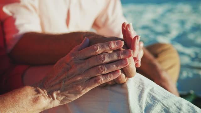 mittelteil des älteres paar hand in hand am strand - seniorenpaar stock-videos und b-roll-filmmaterial