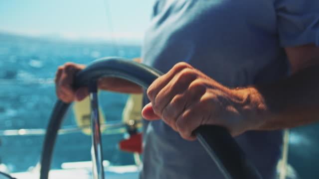 midsection of senior man steering yacht in summer - яхта стоковые видео и кадры b-roll