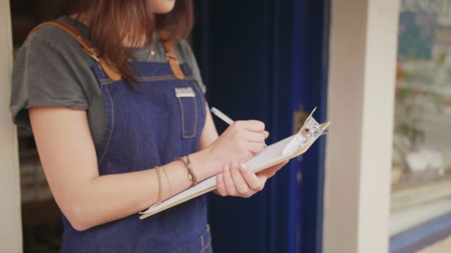 Midsection Of Small Business Owner Writing In Clipboard Outside Shop video