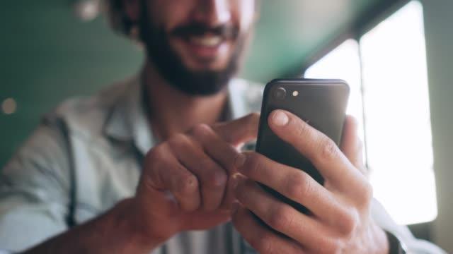 midsection of smiling blogger using smart phone - młodzi mężczyźni filmów i materiałów b-roll