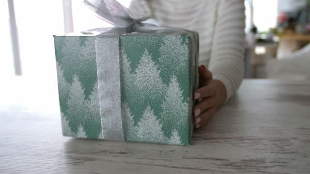 カメラに向かってテーブルの上にクリスマスプレゼントをスライドさせる認識できない若い女性の中間部 - プレセントの箱点の映像素材/bロール