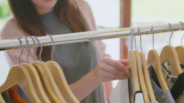 Midsection of woman choosing clothes from metal rack at home Closeup handheld shot of woman choosing clothes from metal rack at home. Midsection of young female hipster wearing casuals. She is sliding hangers on rod. 4K Resolution. coathanger stock videos & royalty-free footage