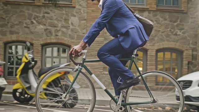 Mid-section slow motion video of businessman riding a  bicycle in the city