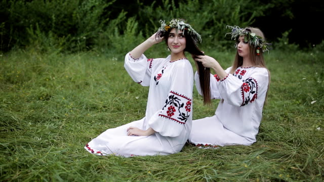 midsummer. two girls in the slavic clothes weave braids in the hair near the fire. - верующий стоковые видео и кадры b-roll