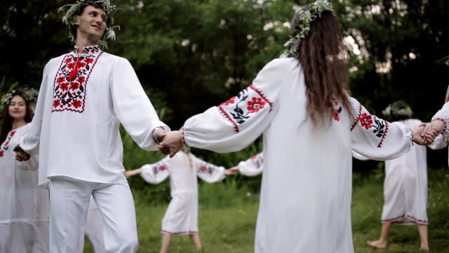 midsummer. young people in slavic clothes revolve around a fire in the midsummer. . - верующий стоковые видео и кадры b-roll
