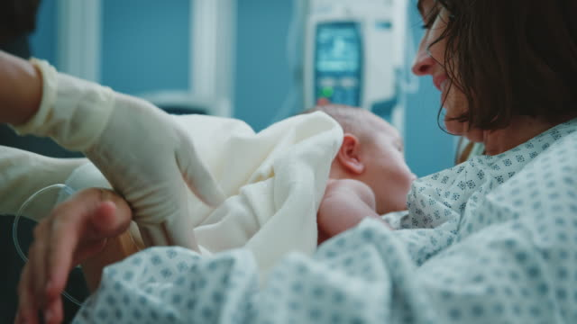 Midwife giving newborn to mother in delivery room