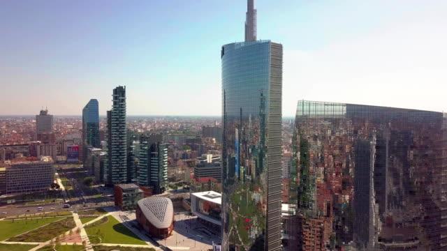vídeos de stock, filmes e b-roll de milão, itália - 26 de setembro de 2018: milão cidade horizonte vista voando em direção de arranha-céus de área financeira - sol nascente horizonte drone cidade