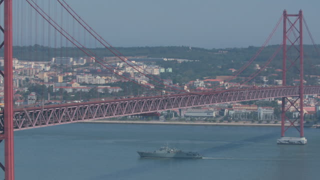 Military boat floating under 25th of April Bridge Military boat floating under 25th of April Bridge in Lisbon, Portugal ponte 25 de abril stock videos & royalty-free footage