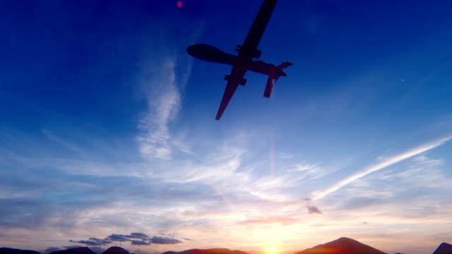 석양에 사막 산 평원을 날아가는 군사 무인 항공기 - 무인항공기 스톡 비디오 및 b-롤 화면