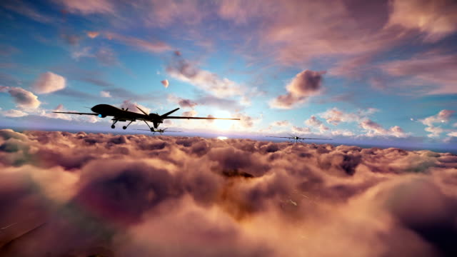 Military drones formation launching missiles, cruising above clouds at sunset video