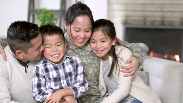 Military Family Sitting On Couch A family of four is happily sitting on the sofa in their living room. The mother has just returned home from serving her country and is wearing a military uniform. military lifestyle stock videos & royalty-free footage