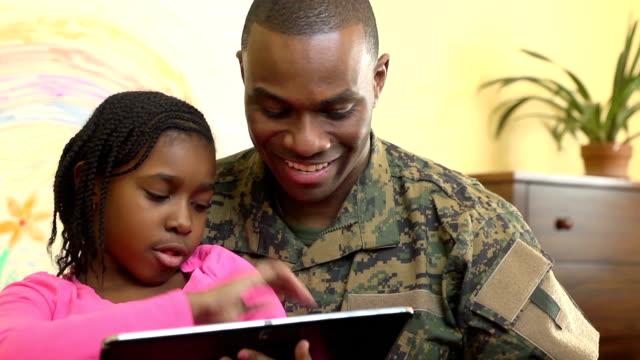 militär vater spielt auf digitale tablet mit tochter - wohngebäude innenansicht stock-videos und b-roll-filmmaterial