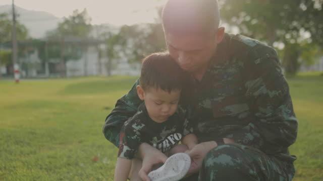 vidéos et rushes de père de militaire attacher le lacet de son fils dans un parc - ligoté
