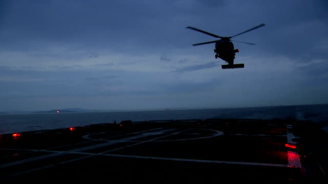 Military helicopter lands on the deck of a battleship Military helicopter lands on the deck of a battleship medevac stock videos & royalty-free footage