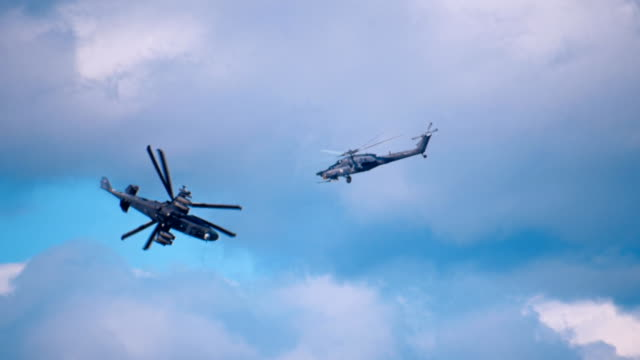 Military helicopters flying on a background of clouds Two military helicopters: reconnaissance and attack helicopter of the new generation Ka-52