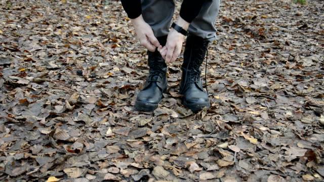 Military man in uniform tying brown shoelaces on military boots video