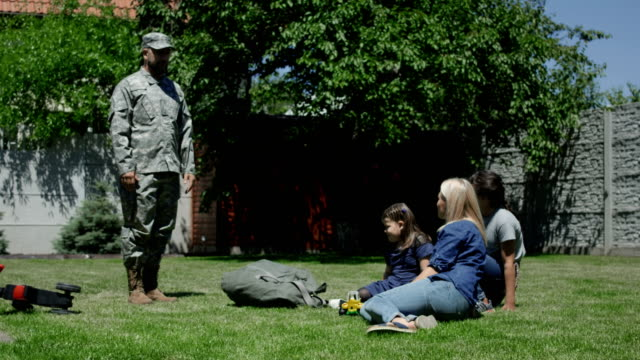 Military man spending time with family Adult man wearing military uniform and having fun with kids and wife in backyard in summertime homecoming stock videos & royalty-free footage