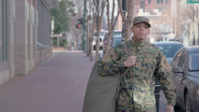 Military Man Walks on Urban Street Setting Military Man walks on urban street. veteran stock videos & royalty-free footage