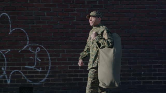 Military Man Walks on Urban Street Setting video