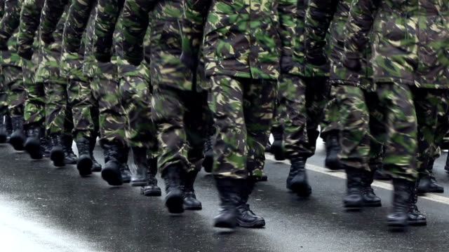 Military Marchpast Close-up shot with soldiers in black boots and camouflage green uniforms march along the wet road. military private stock videos & royalty-free footage