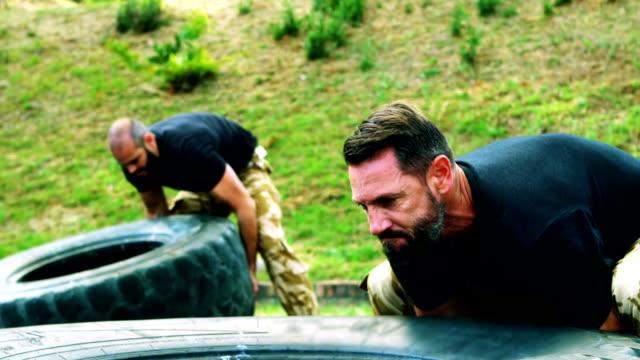 Military men lifting a big tire