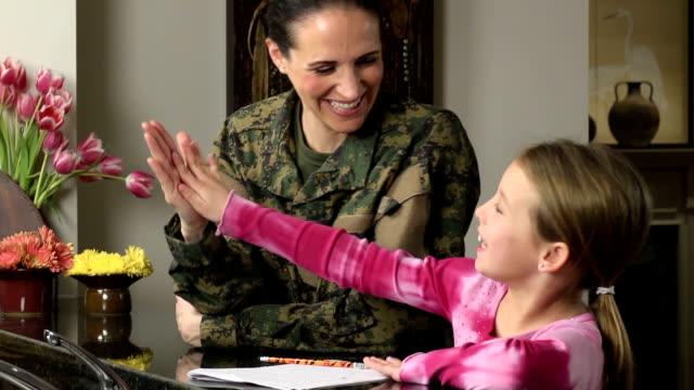 vídeos de stock e filmes b-roll de militar mãe ajuda a menina com trabalhos de casa - fuzileiro naval