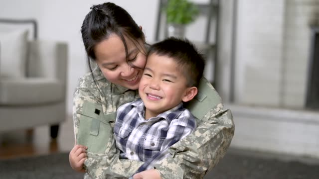 Military Mom Hugging Her Son A mother and her son are hugging in their living room. The mother is wearing a military uniform. military lifestyle stock videos & royalty-free footage