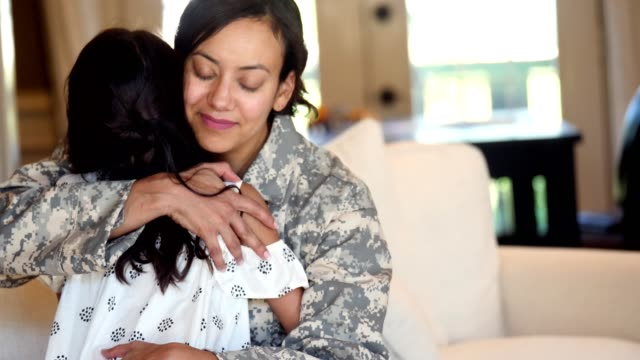Military mom is sad to leave her young daughter Elementary age girl gives her mom a big hug before her mom leaves for military assignment. The woman opens her arms and embraces her daughter. veteran stock videos & royalty-free footage