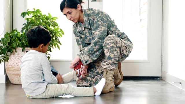 military mom teaches son to put on his shoes - military lifestyle stock videos & royalty-free footage