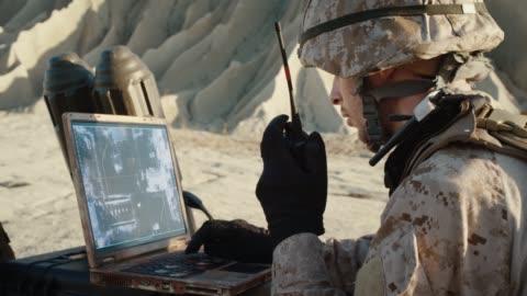 stockvideo's en b-roll-footage met militaire operatie in de woestijn, met satelliet- of drone technologie: soldaat met laptop controleert verkeer van gewapende terroristische voertuig, maakt gebruik van radiocommunicatie bel een luchtaanval. - communicatie