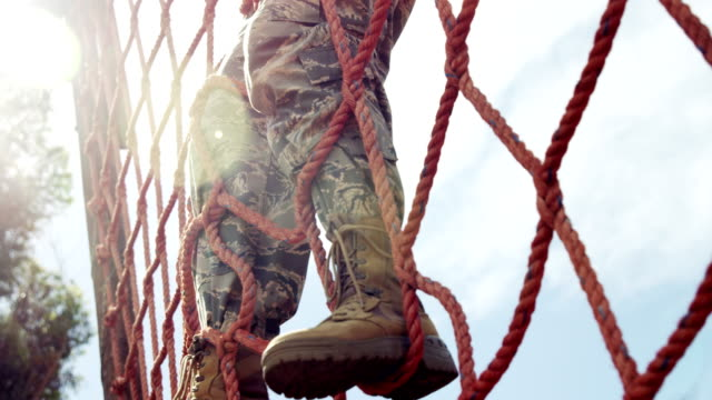 vídeos de stock e filmes b-roll de military soldier climbing a net during obstacle course 4k - bota