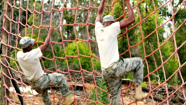 Military soldier climbing rope during obstacle course video