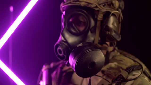 A military soldier in modern equipment and a gas mask holds a rifle in his hands. The concept of war in the modern world