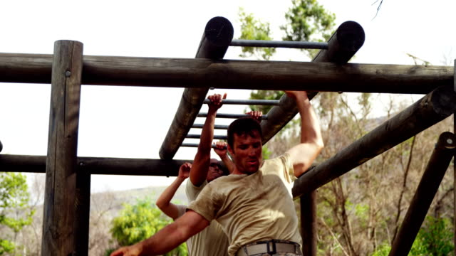 Military soldiers climbing monkey bars 4k video