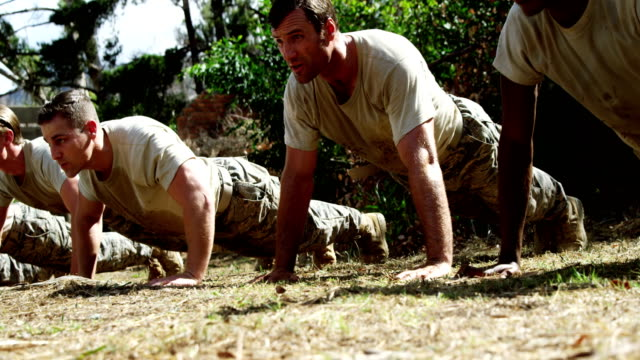 Military soldiers dosing push-ups during obstacle course 4k Military soldiers dosing push-ups during obstacle course at boot camp 4k military uniform stock videos & royalty-free footage