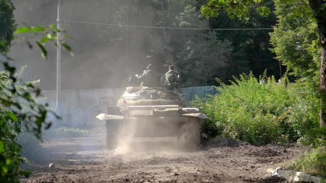 vídeos de stock e filmes b-roll de military soldiers sitting on war tank moving on road at shooting range - cisterna água parada
