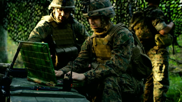 Military Staging Base, Officer Gives Orders to Chief Engineer, They Use Radio and Army Grade Laptop. They're in Camouflaged Tent in a Forest. They're on Reconnaissance Operation/ Mission. video