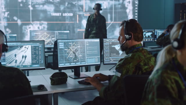Military Surveillance Officer Working on a City Tracking Operation in a Central Office Hub for Cyber Control and Monitoring for Managing National Security, Technology and Army Communications. Military Surveillance Officer Working on a City Tracking Operation in a Central Office Hub for Cyber Control and Monitoring for Managing National Security, Technology and Army Communications. military stock videos & royalty-free footage