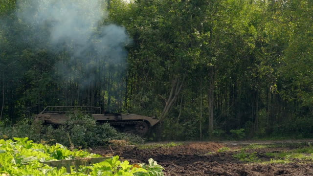 Military tank breaks down green trees to build road in forest for fight enemy Military tank breaks down green trees to build road in forest. Armored vehicle on shooting range moving on green forest. Military tank destroy naturefor fight with enemy storage tank stock videos & royalty-free footage