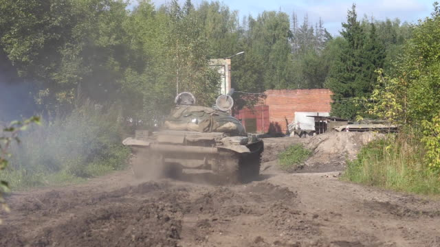 vídeos de stock e filmes b-roll de military tank driving on road on background destroyed building slow motion - cisterna água parada