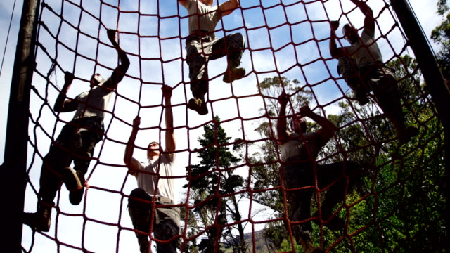 military troops climbing a net during obstacle course 4k - armia filmów i materiałów b-roll