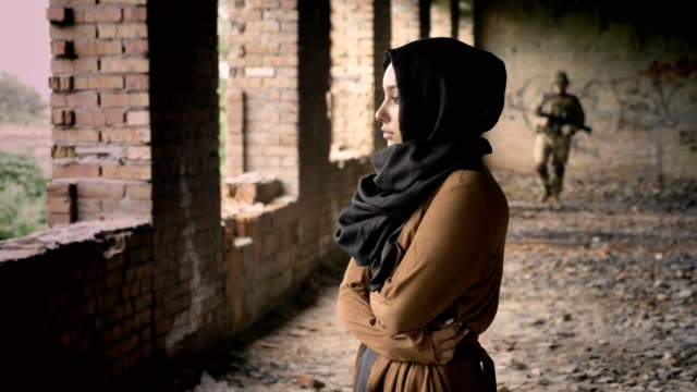 military, young muslim woman standing in abandoned building, soldier walking towards woman with scared and sad expression - fuggitivo video stock e b–roll