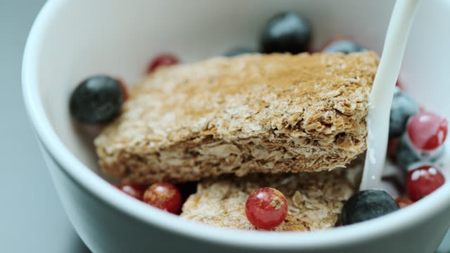 SLO MO milk being poured onto oat bars with fruit video