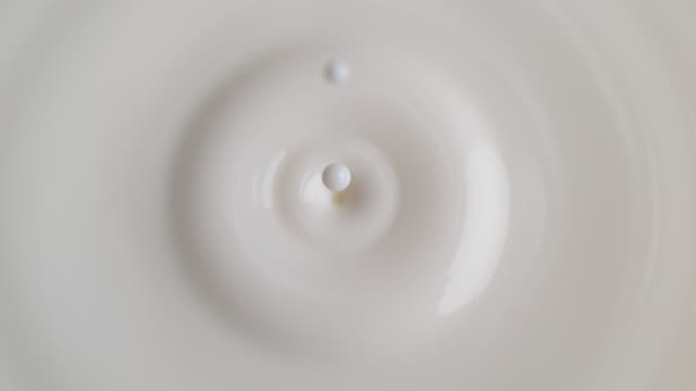 beyaz kremsi sıvıiçine düşen süt damlası - dalga dalga yayılma stok videoları ve detay görüntü çekimi