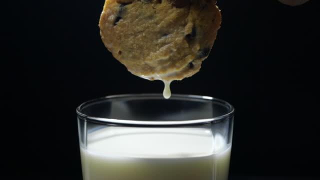 goccia di latte da un biscotto al cioccolato al rallentatore - immergere video stock e b–roll
