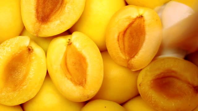Milk flow fills apricot slices video