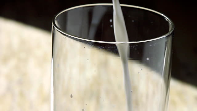 Milk is poured into a glass on a wooden table video
