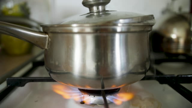 milk or soup is boiled and flowed away on the stove - pentola video stock e b–roll